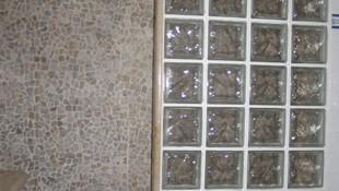 Formación de plato de ducha en interior cueva. El revestimiento de las paredes y del plato de ducha con piedra natural.