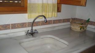Detalle de banco de cocina y fregadero, en una pieza, de mármol Macael Blanco.
